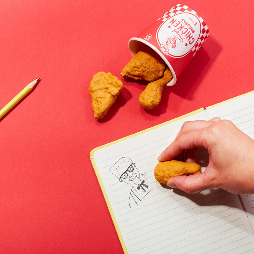 A paper bucket that is slightly larger than a fist filled with erasers that look like pieces of fried chicken
