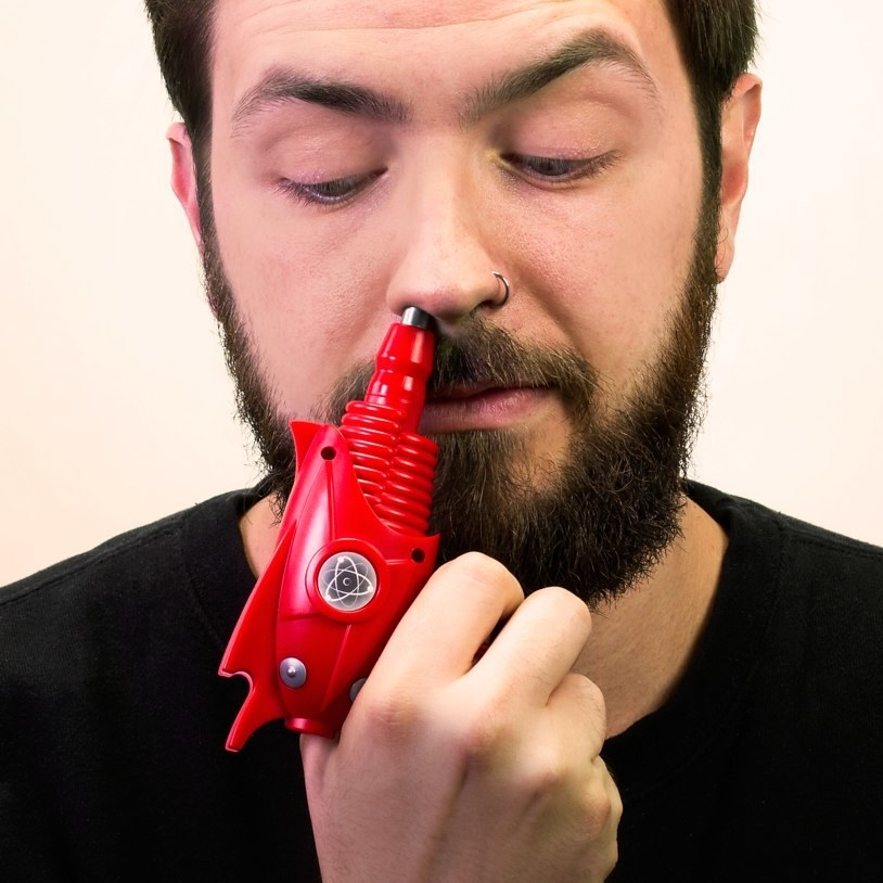 A person sticking the cartoonish ray gun into their nose to shave it