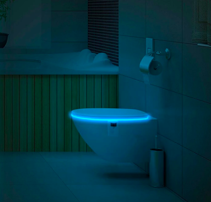 A toilet with the seat closed and a light glowing from inside the bowl
