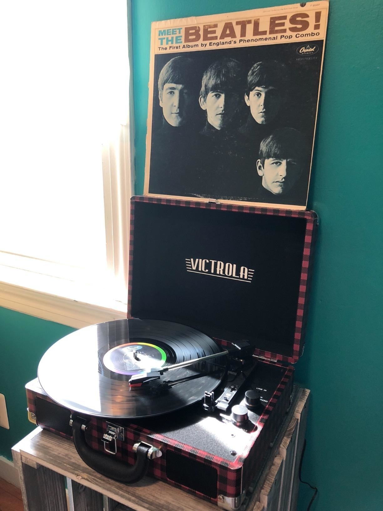 "reviewer's black and red plaid record player playing ""meet the beatles"""