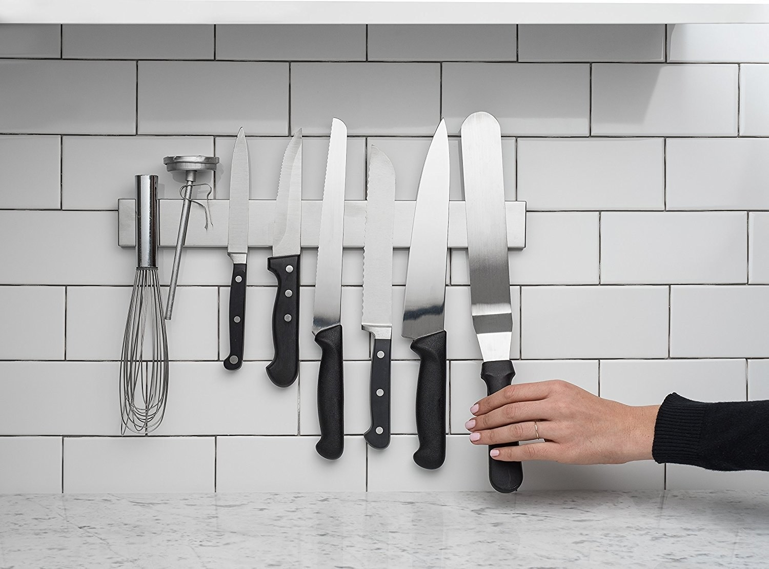 kitchen backsplash with white subway tile with stainless steel metal knife magnetic holder on wall