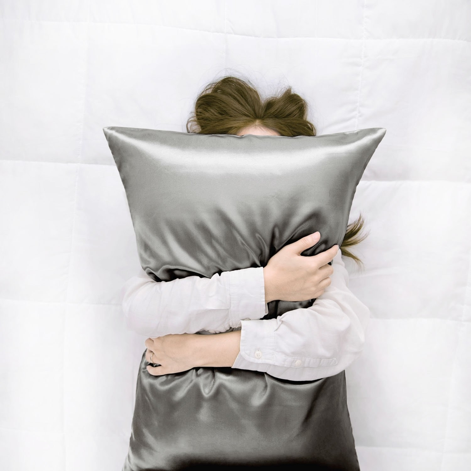 A model clutching a shiny grey satin pillow