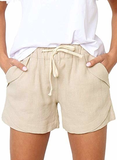 a model wearing the shorts in light tan with their hands in the pockets
