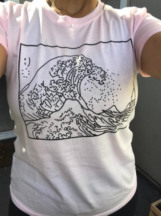 a close up on the tee which has a wave crashing on it