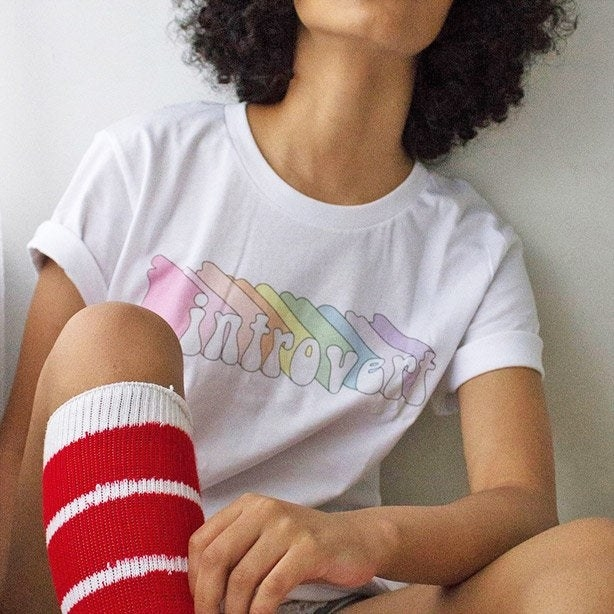 "a model wearing a white tee with a graphic illustration of ""introvert"" in rainbow colors"