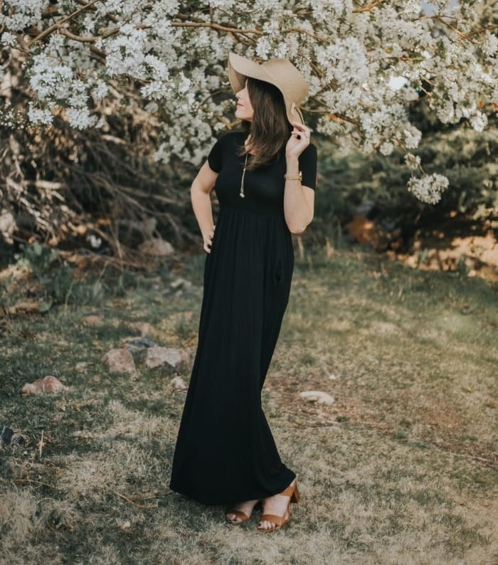 Reviewer wearing the maxi dress in black with a floppy hat and sandal heels