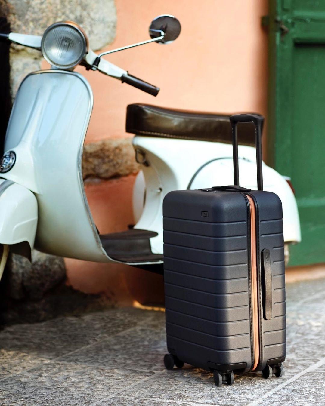 navy blue away suitcase next to a vespa