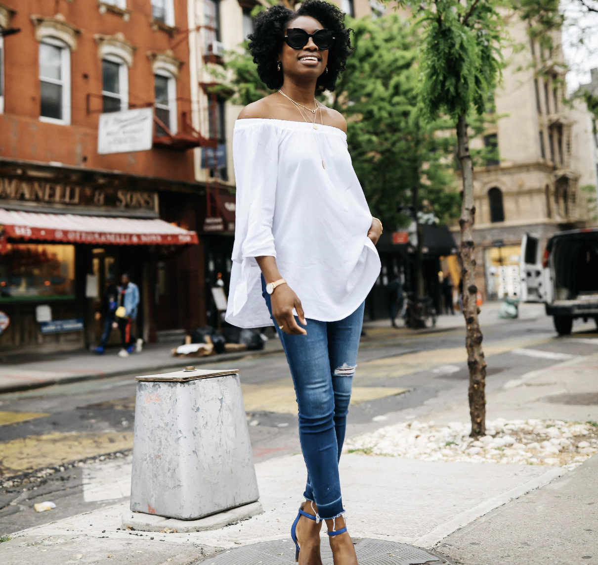 Model wearing flowy top with three-quarter sleeves in white with jeans and heels