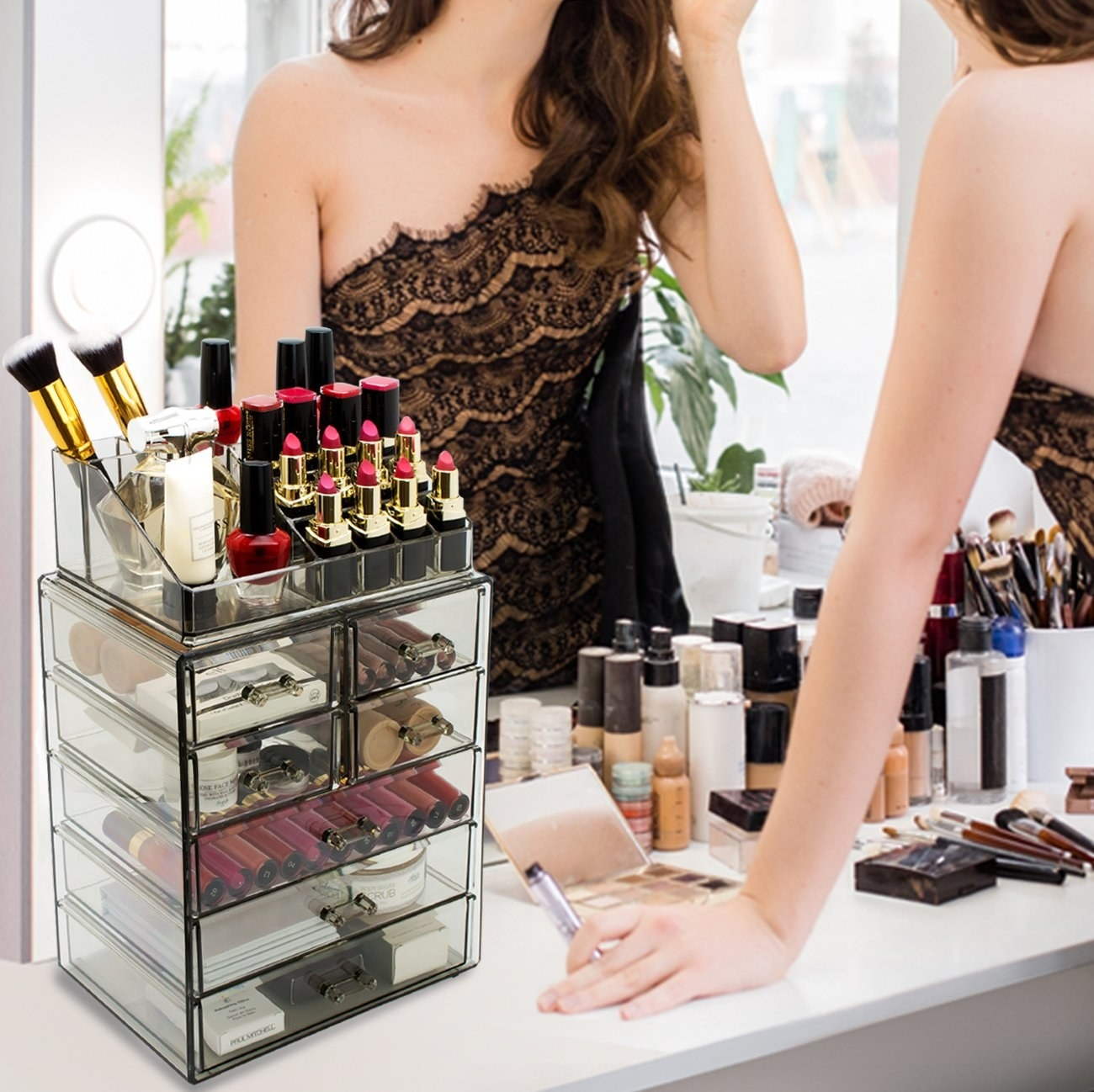 The organizer on a counter holding lipsticks, brushes, lashes, and other makeup