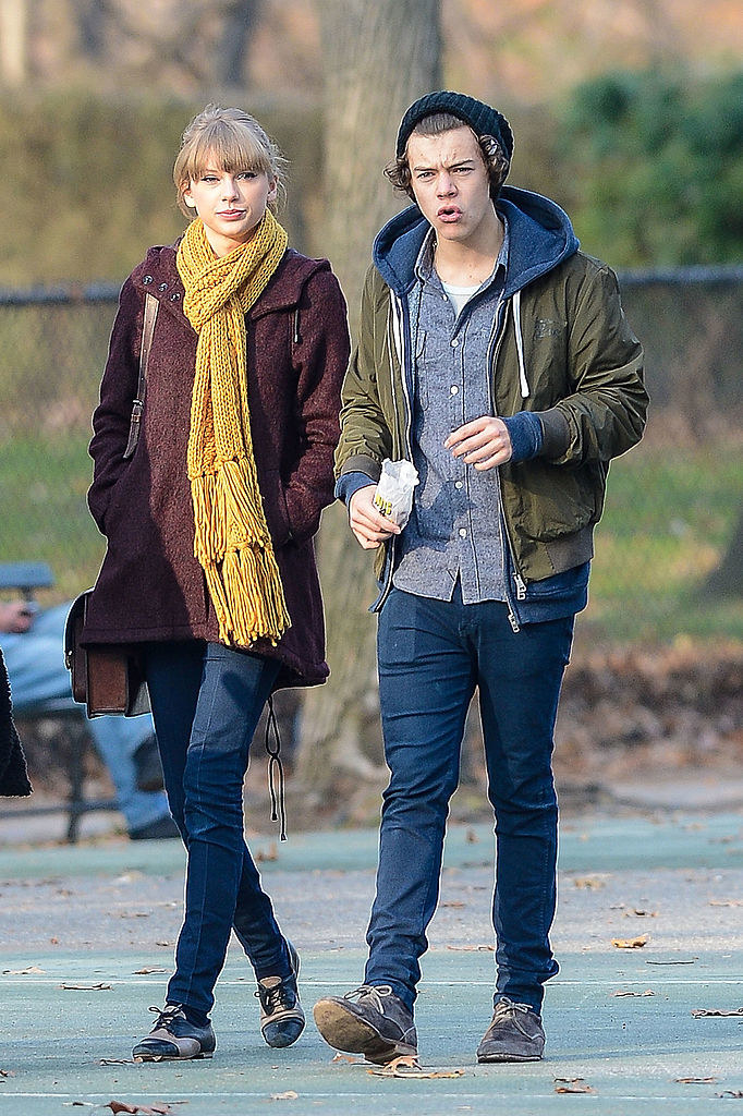 taylor swift in a scarf walking next to harry styles