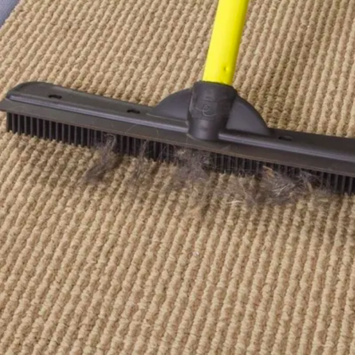 Closeup of rubber bristles pulling hair from carpet
