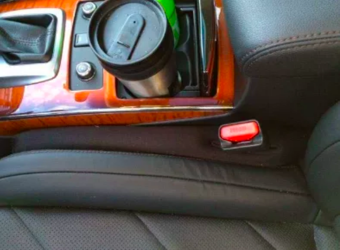 The filler placed over the entire gap between the driver's seat and the console. There's a hole for the seat belt buckle.