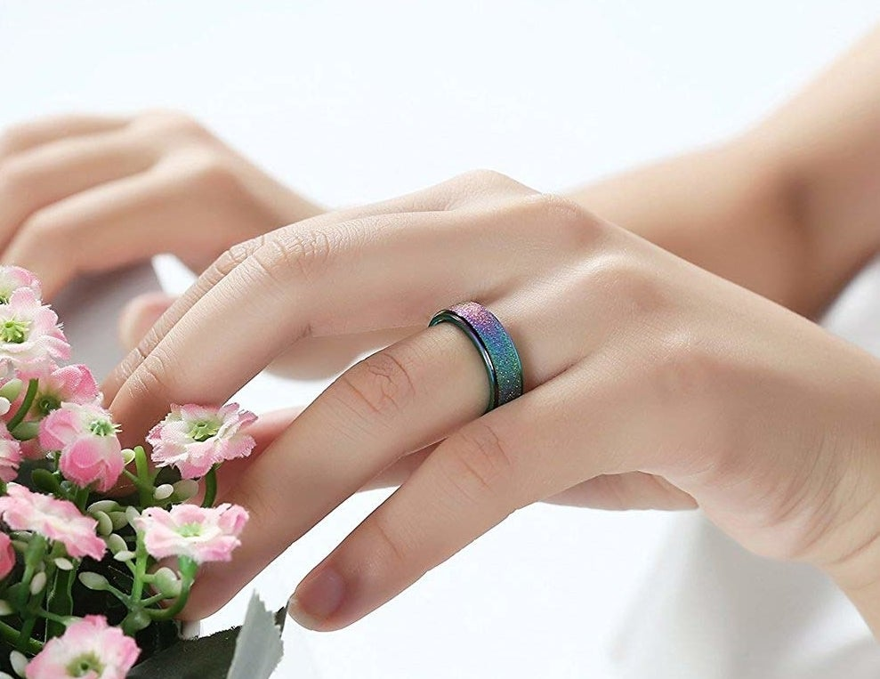 Hand wearing the iridescent ring