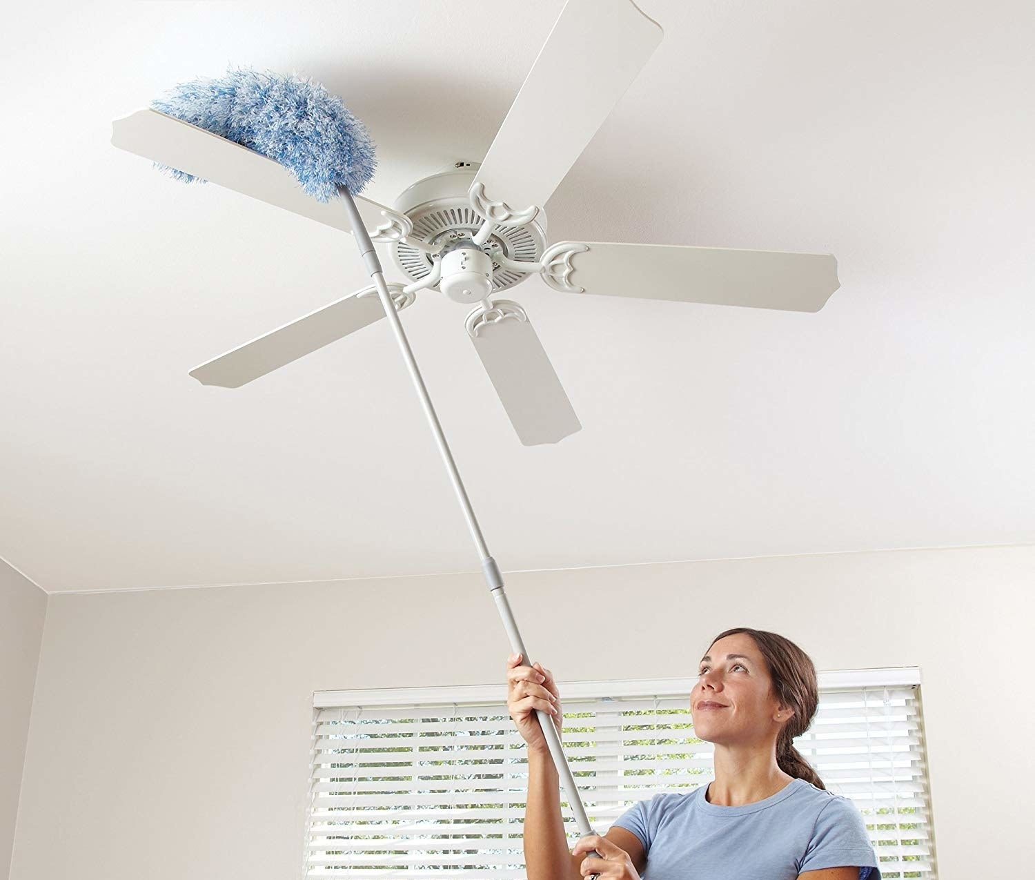 long handled duster being used on ceiling fan