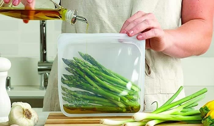 Model holding a clear silicone bag with asparagus inside and olive oil being poured inside