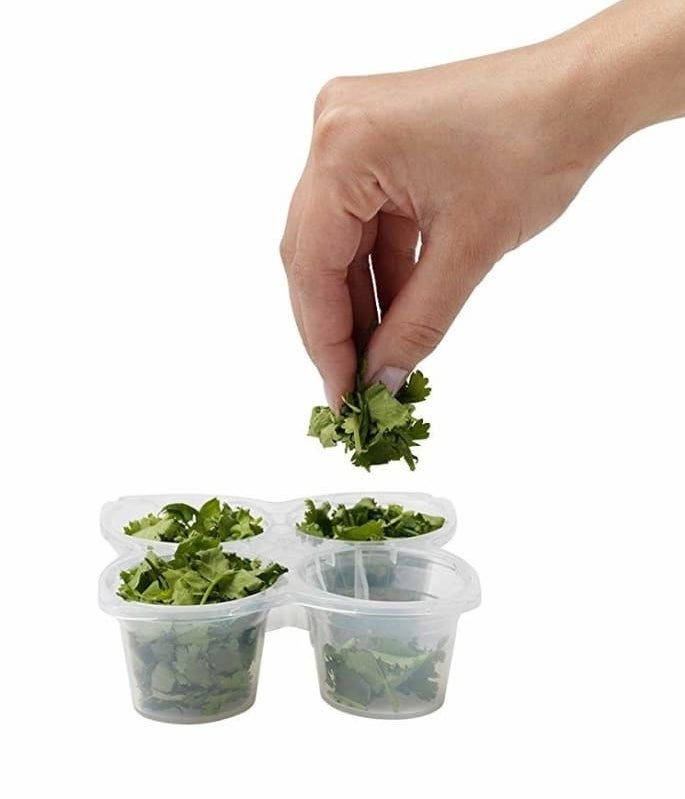 A tray with four connected cups filled with herbs and a model's hands taking a few herbs out of one of the cups