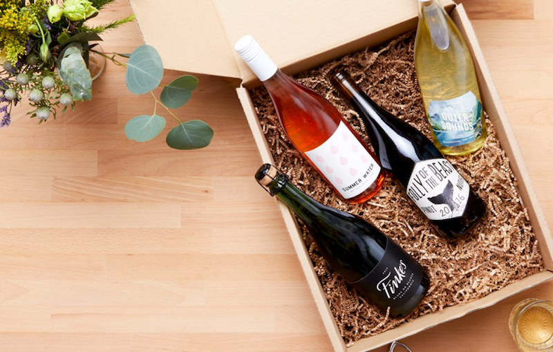 Photo showing four bottles of wine in a Winc subscription box
