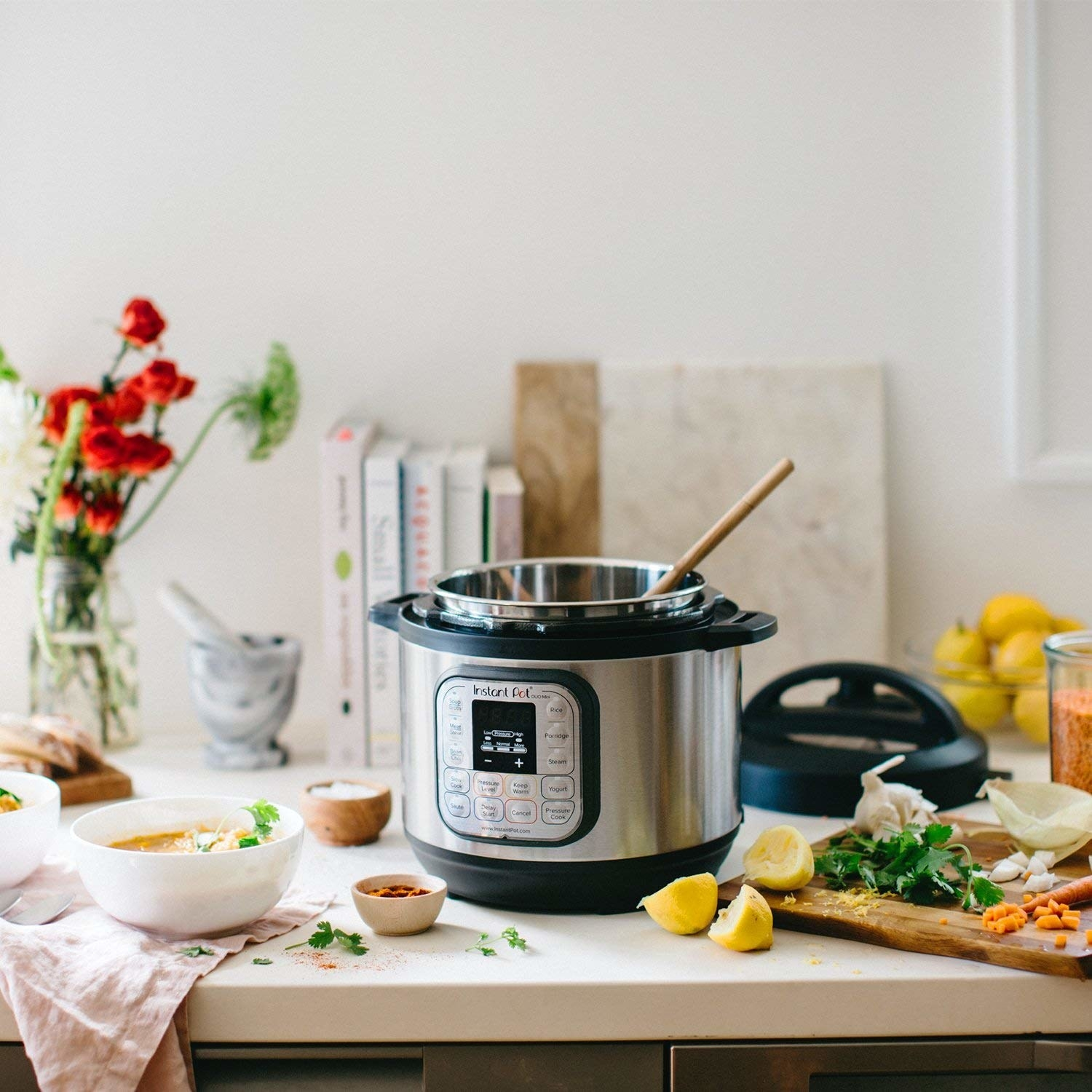 open Instant Pot with wooden spoon sticking out of it on a kitchen counter with a lot of ingredients