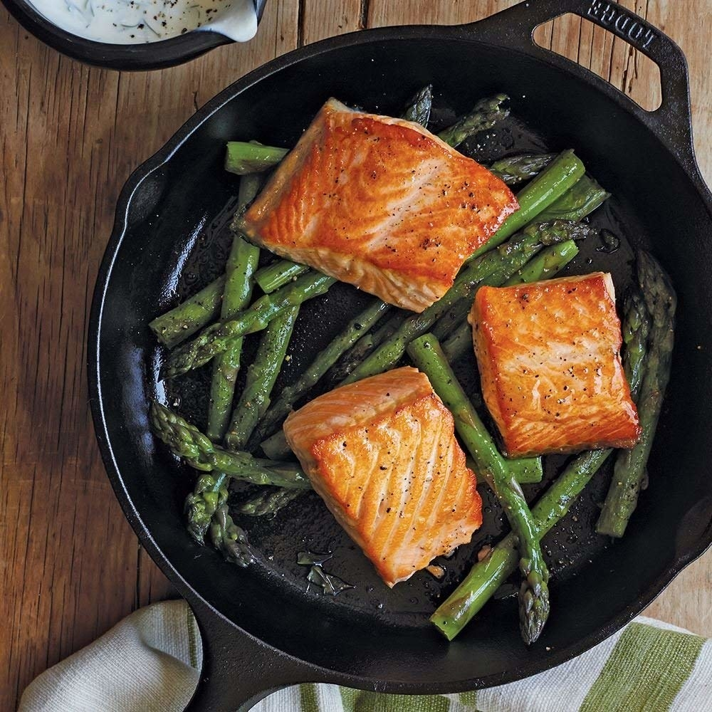 cast iron pan with salmon and asparagus in it