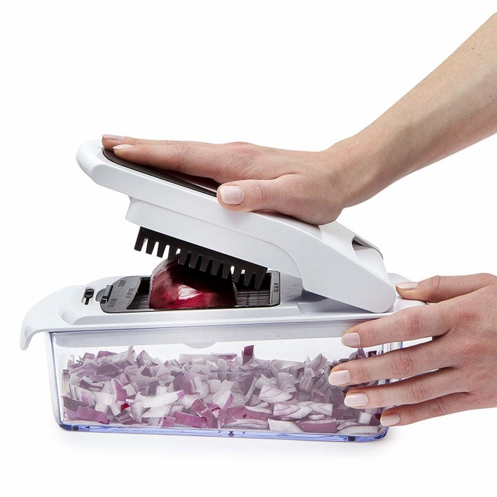 person chopping an onion with the gadget