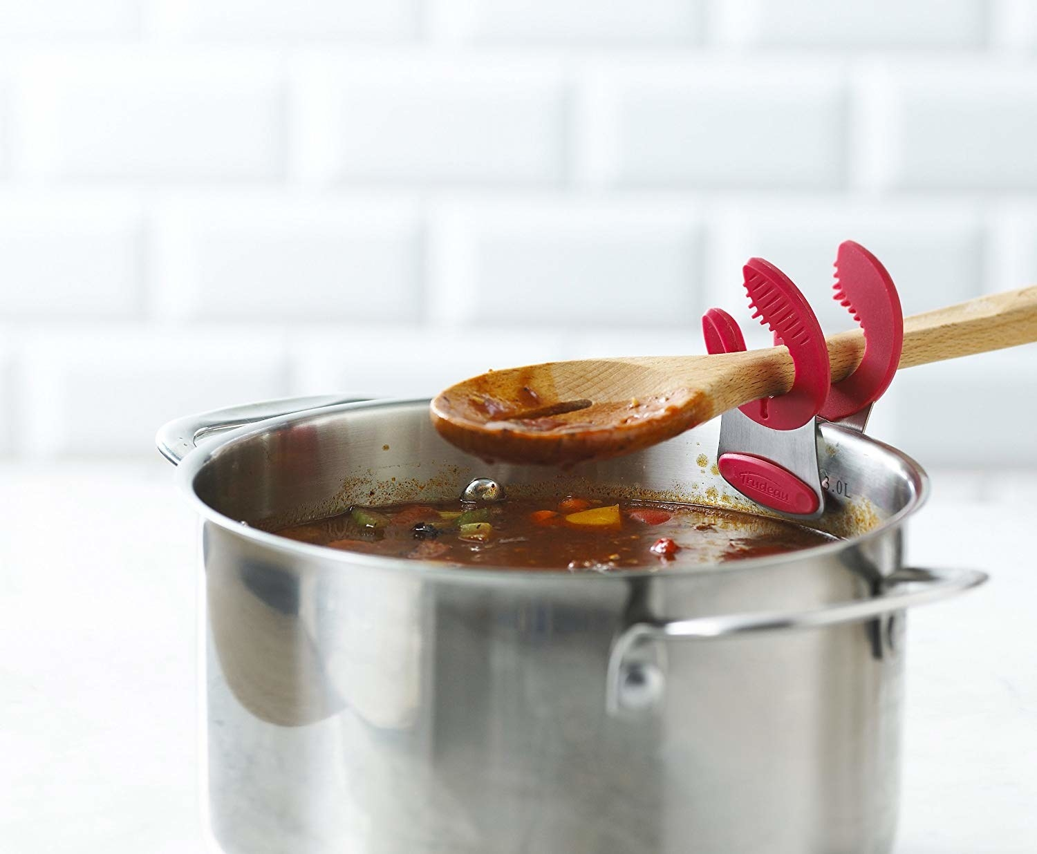 big pot of soup with wooden spoon balanced on clip that looks like a lobster claw
