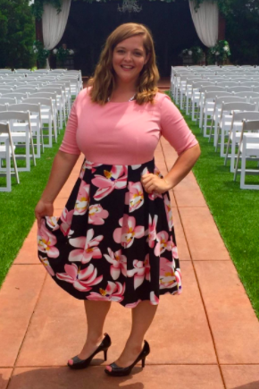 A reviewer wearing the dress with a pink bodice and pink and black skirt