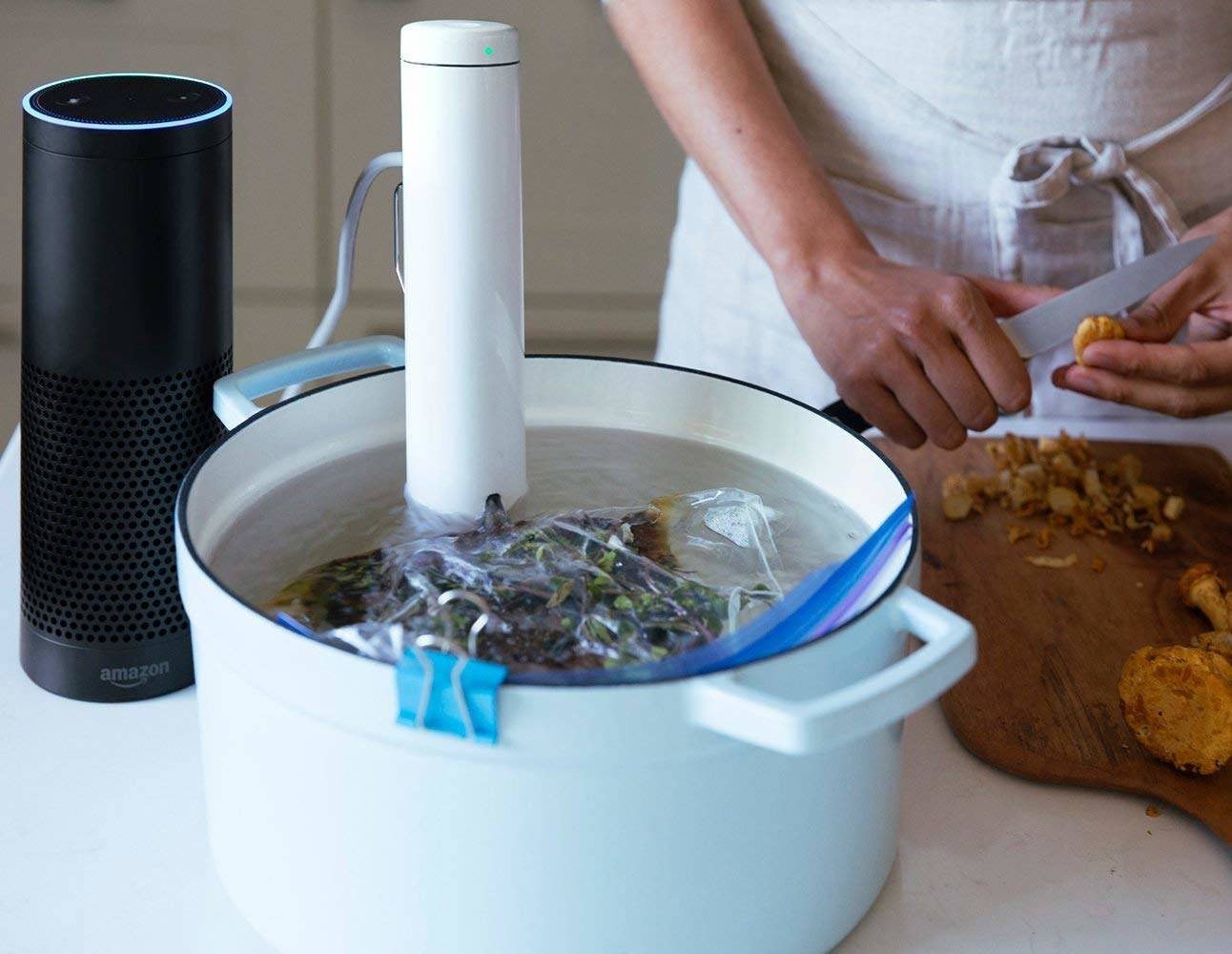 A sous vide chute in a pot of water with food inside a sealed bag