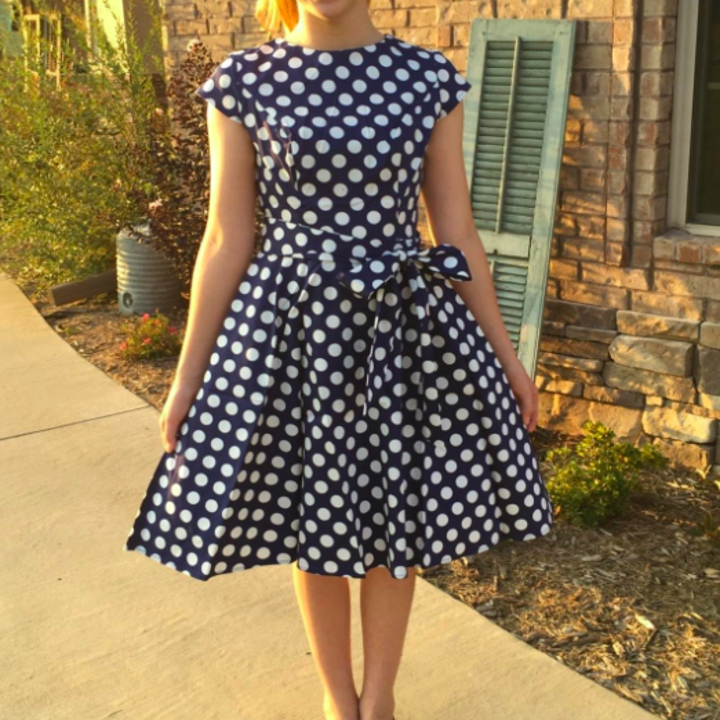 A reviewer wearing the knee-length dress in blue and white polka dots