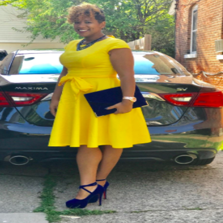 A reviewer wearing the cap sleeve, tie belt, fit-and-flare dress in yellow