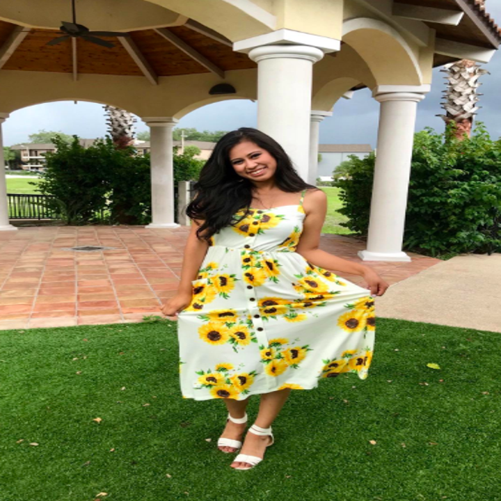 A reviewer wearing the button front sundress in white with yellow sunflowers