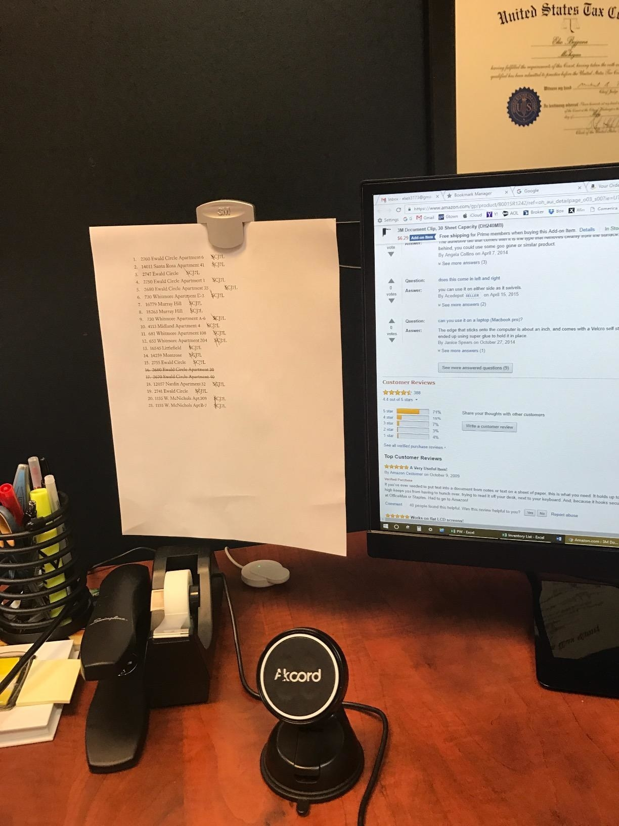 Reviewer photo of the clip holding a document, which is attached to a computer monitor