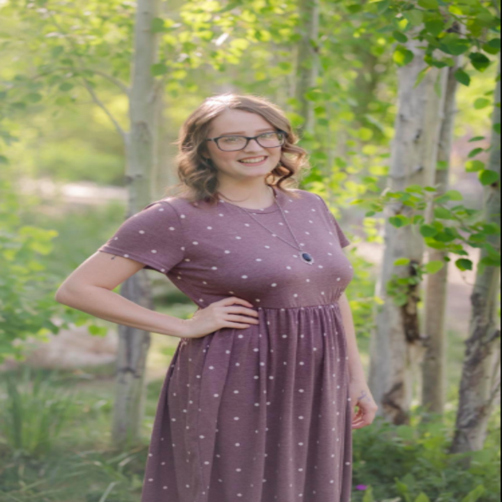 A reviewer wearing the short sleeve dress in brown and white dots