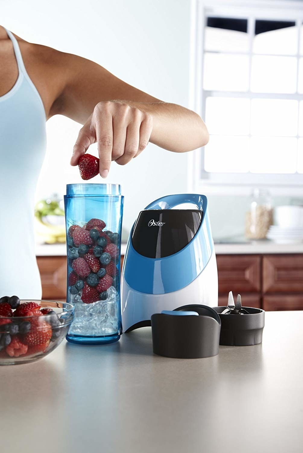 person putting berries and ice into the blender bottle