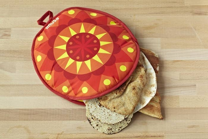 circular tortilla warmer with tortillas and pitas coming out of it