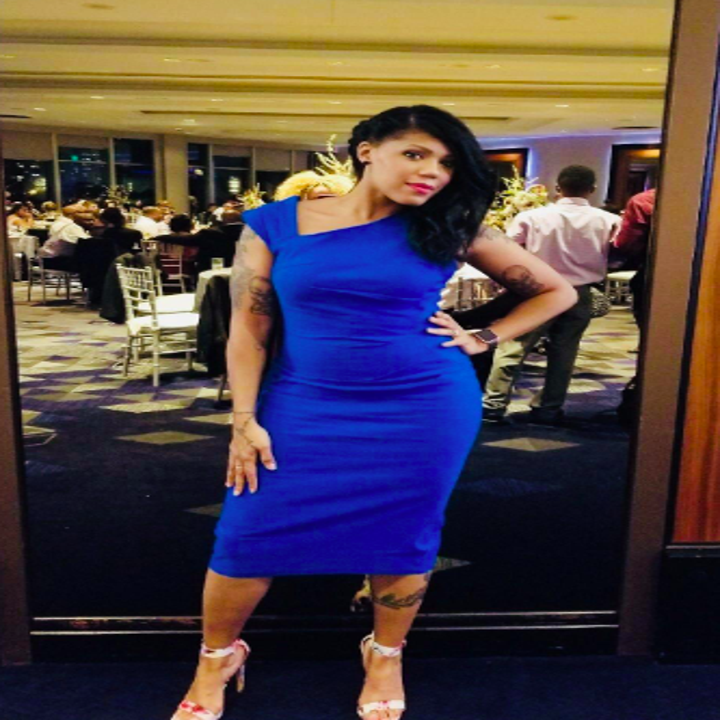 A reviewer wearing the sleeveless, asymmetric strap, below-the-knee dress in blue