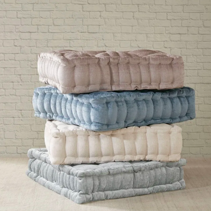 Four plush, square floor pillow stacked on top of each other