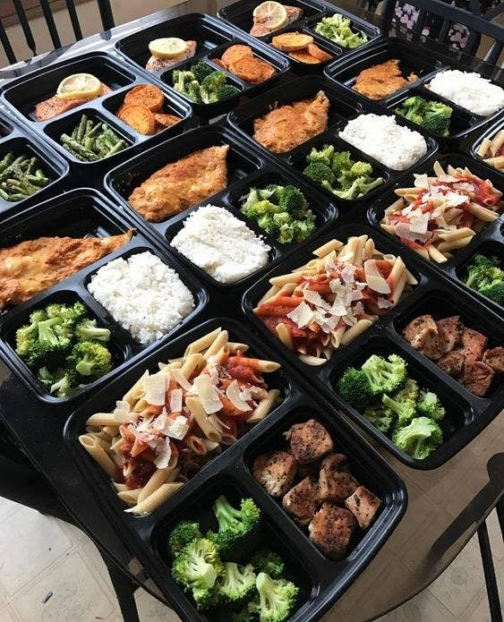 A bunch of the food containers filled with portions of broccoli, rice, noodles, meat, and other foods