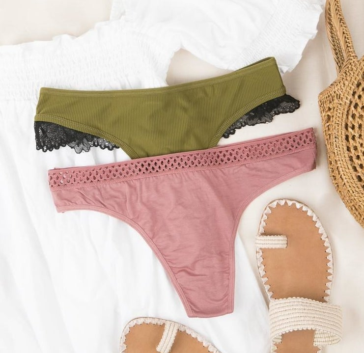 a pair of pink underwear and a pair of green underwear with black lace trim laid out on white fabric