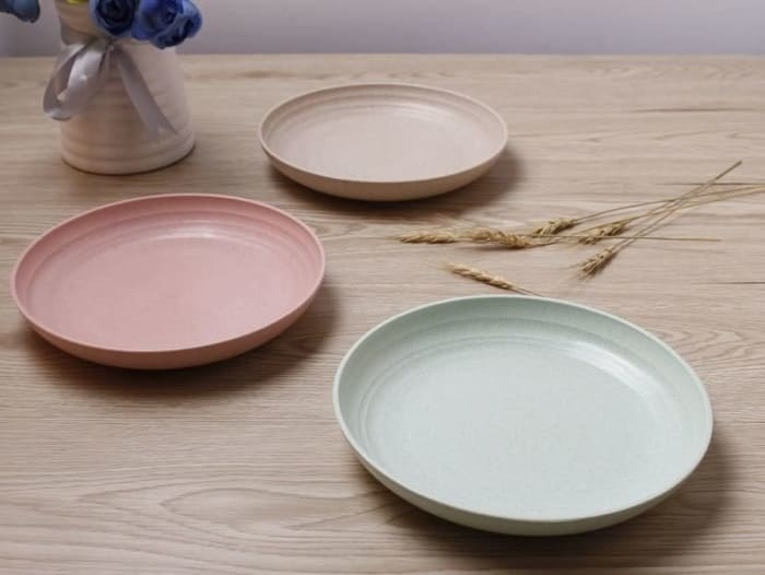 Light blue, pink, and beige plates sitting on a table