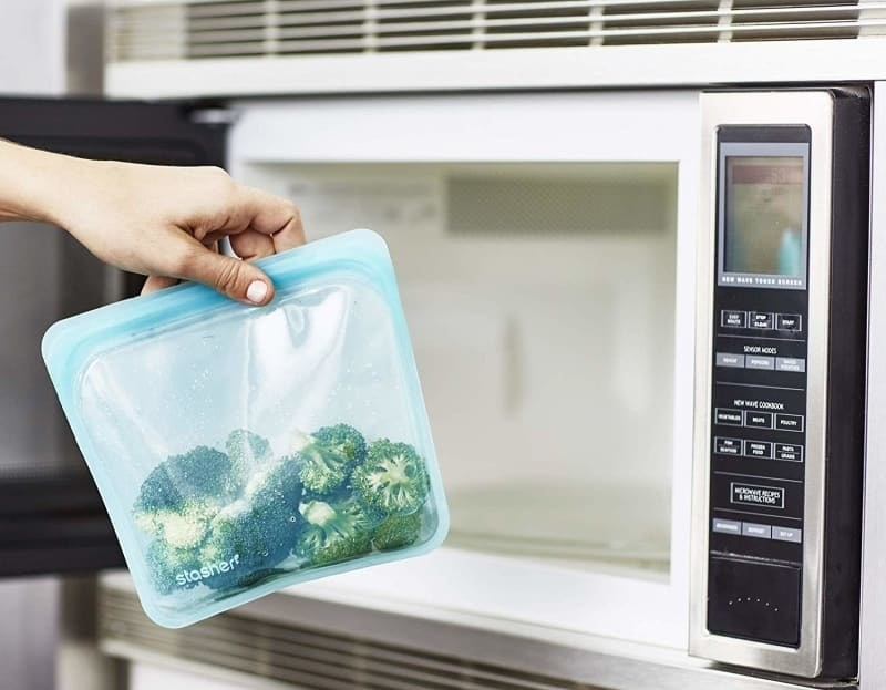 Blue storage bag containing broccoli being placed in microwave