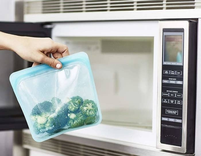 Hand holding the blue silicone bag with broccoli in it being put into the microwave
