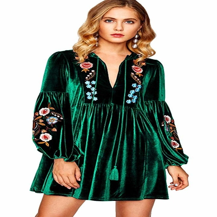 A model in the green, balloon sleeve dress with floral embroidery and tassel ties at the neck