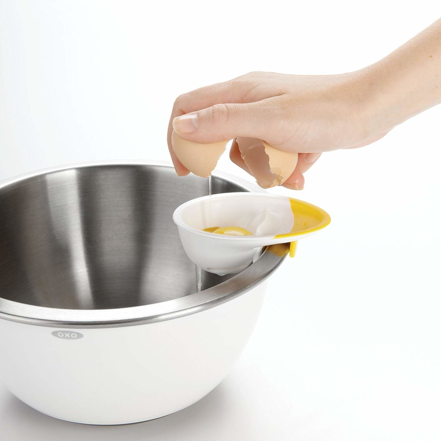 The egg separator attached to the side of a bowl with a model's hand breaking an egg into it