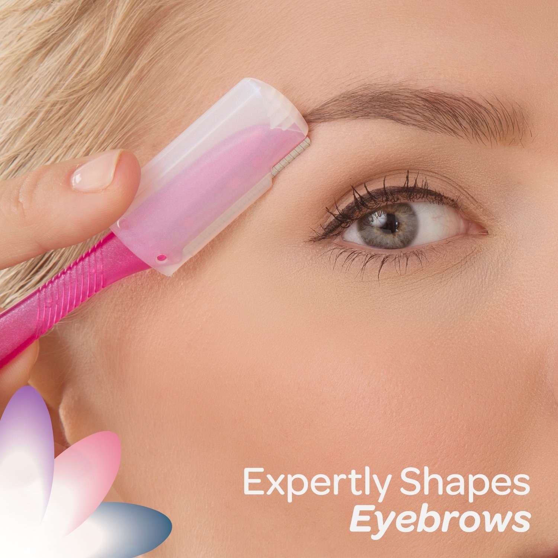 Model using the dermaplaning razor on her eyebrow