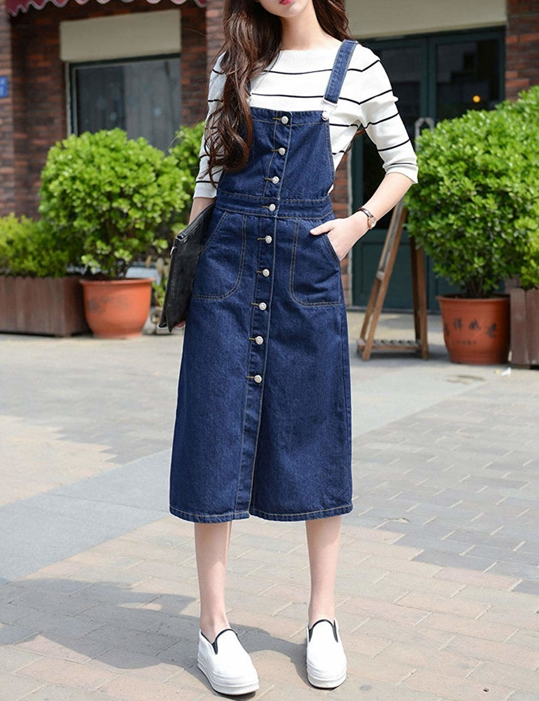 A model wearing the midi-length, button front dress in the dark wash with their hand in one of the side pockets