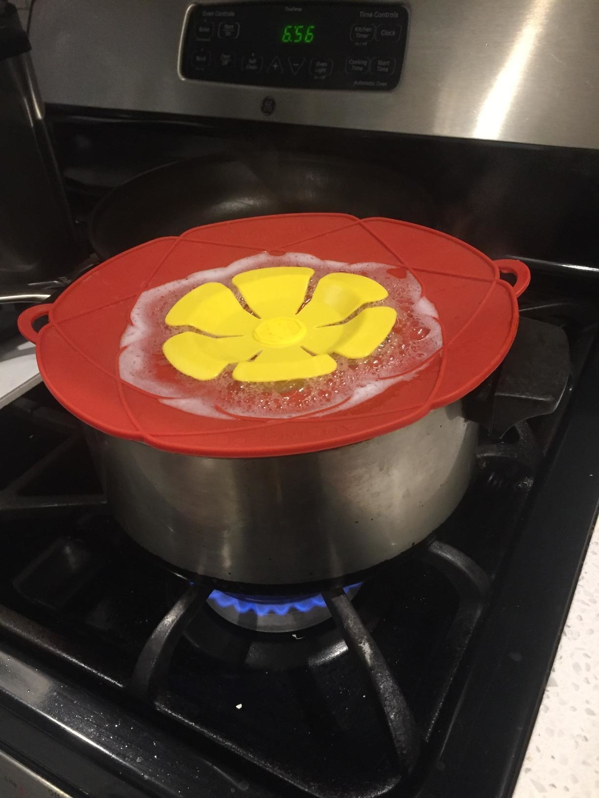 A reviewer stopping their pot boiling over using the silicone cover