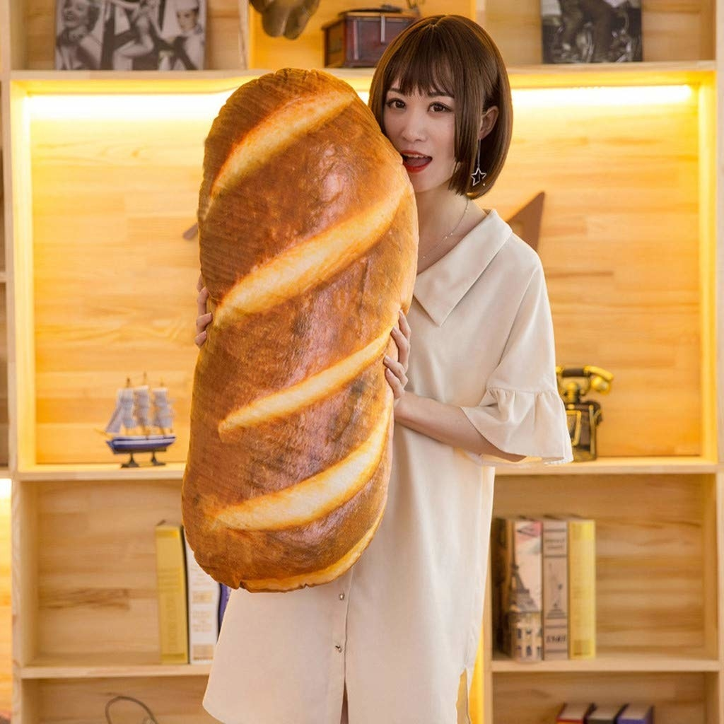 A model posed with a pillow that looks like a loaf of bread
