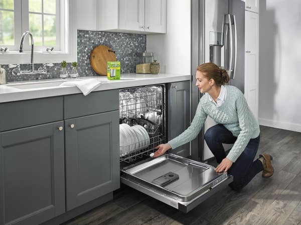 Model putting a tablet in a dishwasher