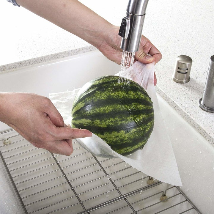 Hands rinsing a watermelon in a paper towel to show the strength