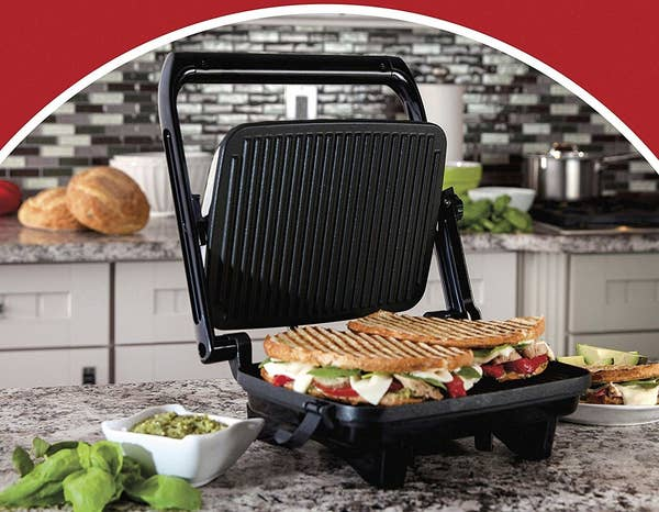 The panini press with a grilled sandwich inside